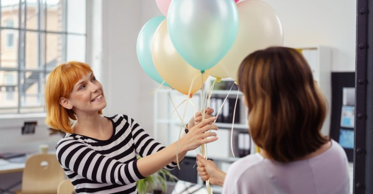 Two female business partners holding balloons